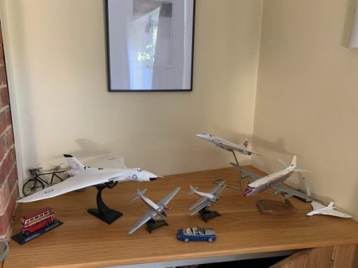 A shelf of models. Mainly planes, but also a bus, car and bicycle.