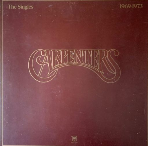 """Album cover of """"Carpenters"""" - """"The Singles 1969-1973"""". Just these words in gold on a plain leather brown background."""