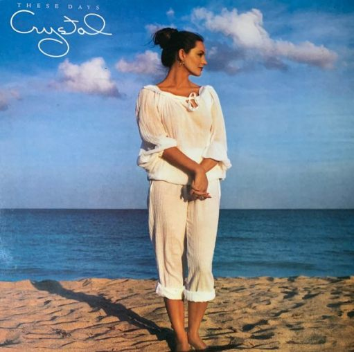 """Album cover - """"These Days"""", Crystal Gayle. Photograph of the artist in a white summer top and trousers on a beach,"""