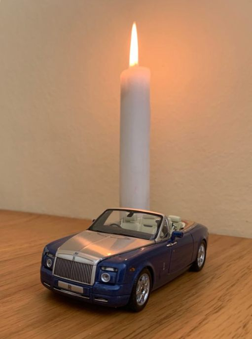 A Candle lit for Diddley, with a model open-top Rolls-Royce in front.