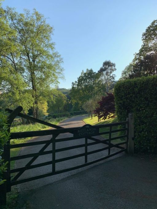 Stylish low wooden gate across the entrance to Kitlands Estate.