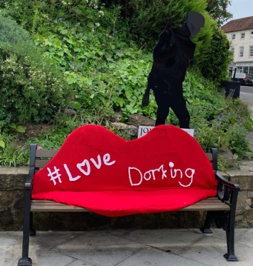 A street bench with a pair of knitted red lips with the words #Love Dorking.