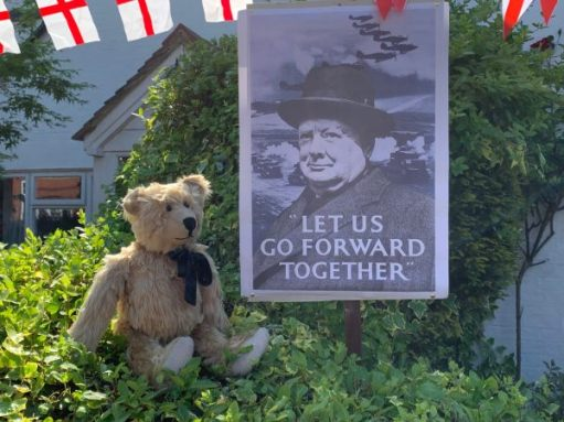 "Bertie sat on a privet hedge alongside a poster of Winston Churchill with the words ""Let us go forward together"" on it."