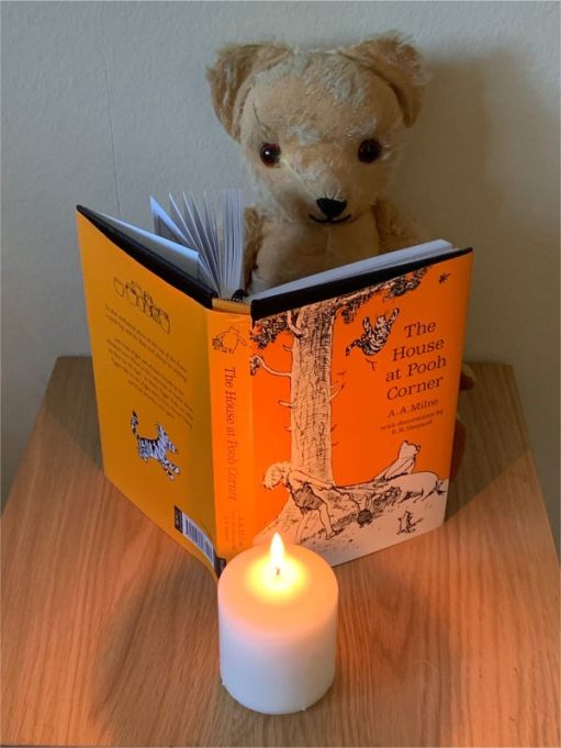 "Eamonn reading ""The House at Pooh Corner"" by AA Milne, with a candle lit for Diddley."