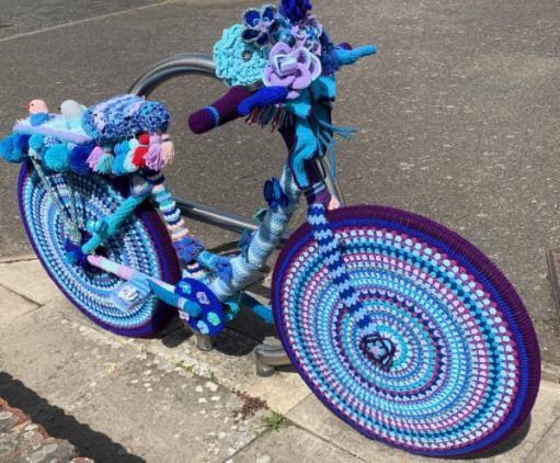 Yarnbomb Sisters - knitted bicycle with concentric circles of various shades of blues and purples on the wheels.