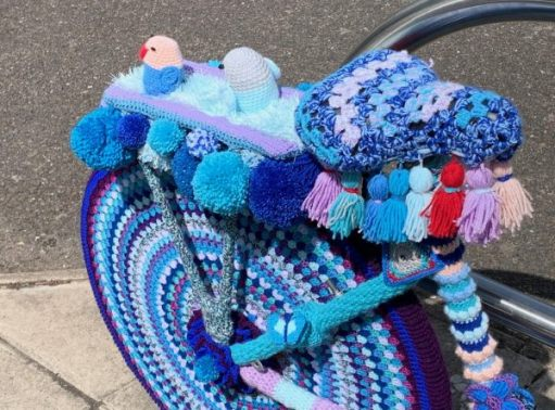 Yarnbomb Sisters - knitted bicycle with penguin scene on rear luggage rack.