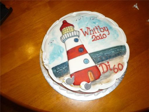 """Birthday Cake. Lighthouse and sea. """"Whitby 2010"""" and """"Di 60""""."""