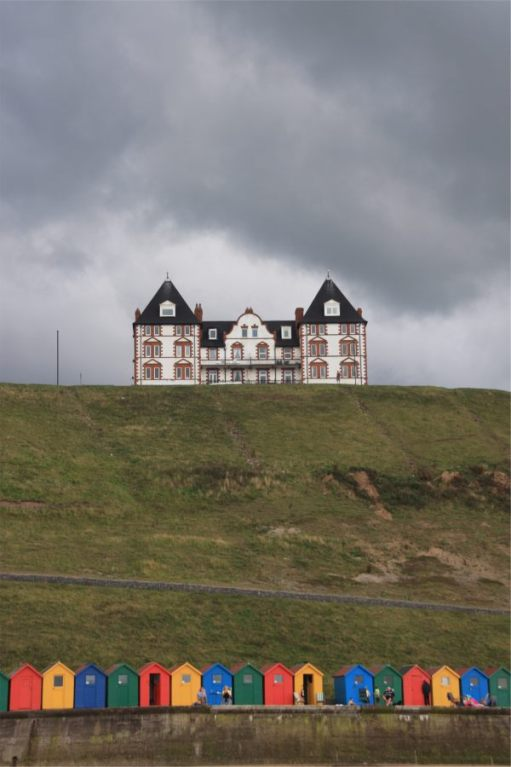 A large house on the cliffs at Whitby, with Beach Huts below.