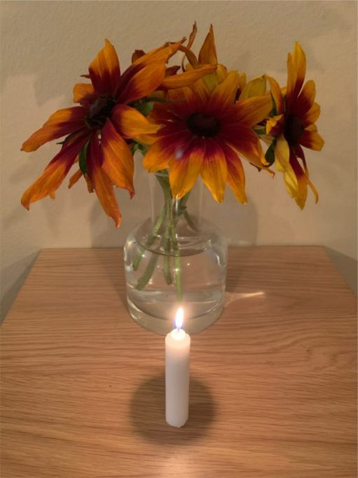 A candle lit for Diddley in front of a vase of Rudbeckias.