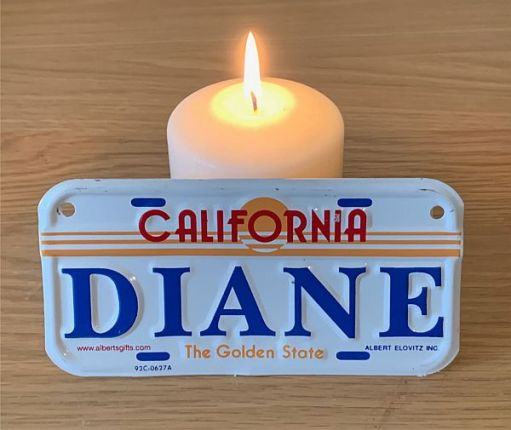 """A candle lit for Diddley, with a Californian licence plate """"Diane"""" in front. A reminder of the trip to Capistrano."""