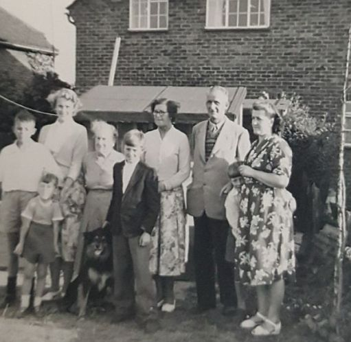 Black & White family photograph outside a semi-detached suburban house.