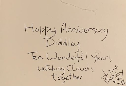 """The handwritten inside of the """"Cloud Watching"""" card: Happy Anniversary, Diddley. Ten wonderful Years watching clouds together. Love Bobby"""" with 9 """"x's"""" in three rows of three underneath."""