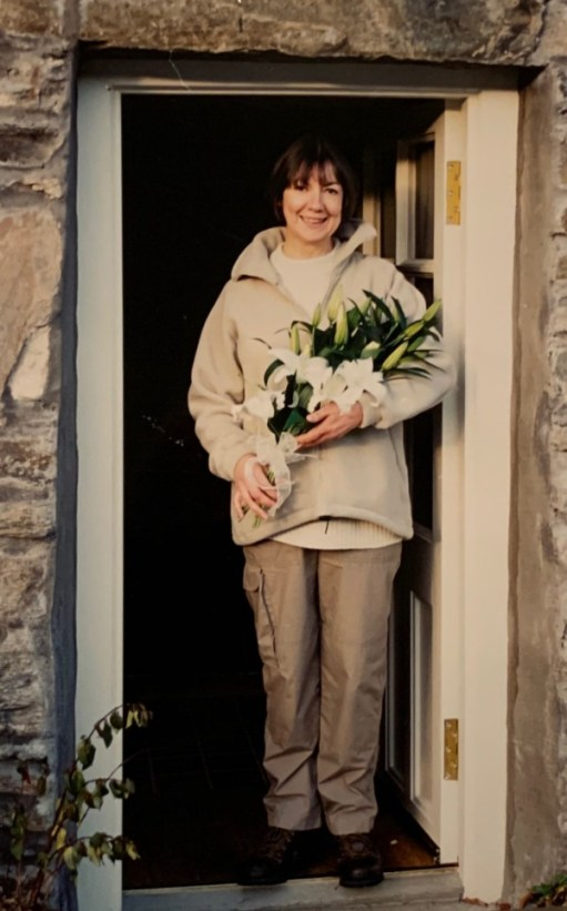 Bride Diddley (in hiking gear) in a doorway holding flowers.