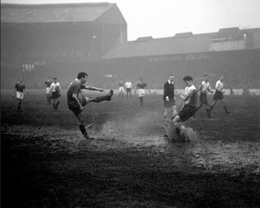 Black and white photograph of Chelsea playing on a soggy, muddy pitch.