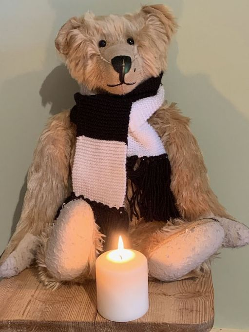 Bertie, wearing his Fulham scarf, sat behind a candle lit for Diddley and Tosh Chamberlain.