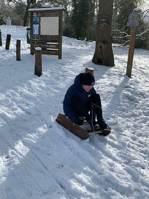 Daisy-Mae sledging down a snowy hill.