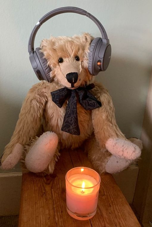 Bertie wearing his headphones sat behind a candle lit for Diddley.
