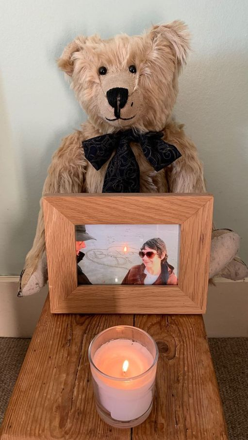 Bertie holding a picture of Bobby & Diddley with a candle in front.