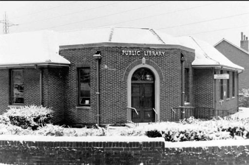 A black and white photograph of the now demolished Ridge Road Library, North Cheam. Taken on a snowy day.