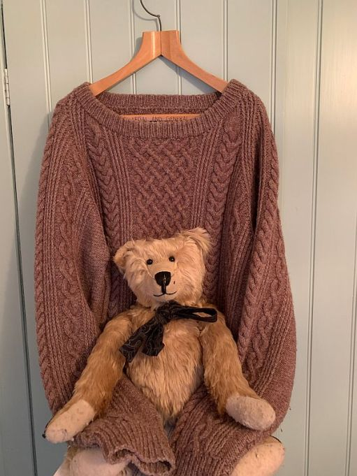Bertie sat on Wendy's Jumper, knitted brown with cable patterning, on a hanger. The sleeves are wrapped around Bertie.
