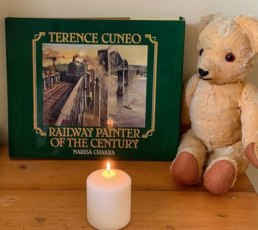 """A candle lit for Diddley in front of the Terence Cuneo book """"Railway painter of the Century2."""
