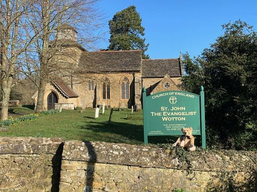 Bertie sat on a wall in front of the sign for Wotton Church, with the church in the background.