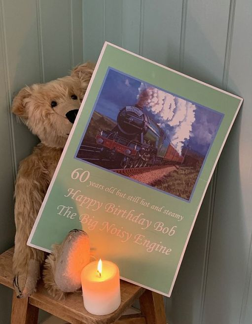 """Bertie, with a candle lit for Diddley and the birthday card from Diddley: A picture of the Flying Scotsman and the text """"60 years old but still hot and steamy. Haooy Birthday Bob the Bog Noisy Engine""""."""