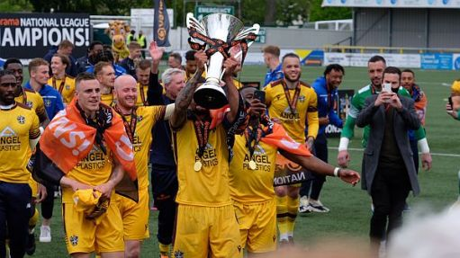 Team doing the lap of honour with the trophy.