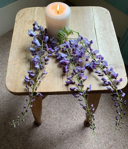 A candle lit for Diddley on a rustic table with some cut Wisteria.