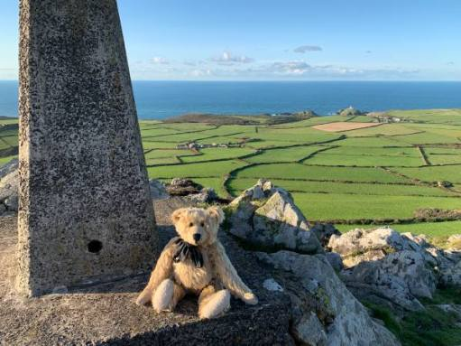 Bertie sat by the Trig Point on top of Garn Fawr, with the ssea in the distance behind.