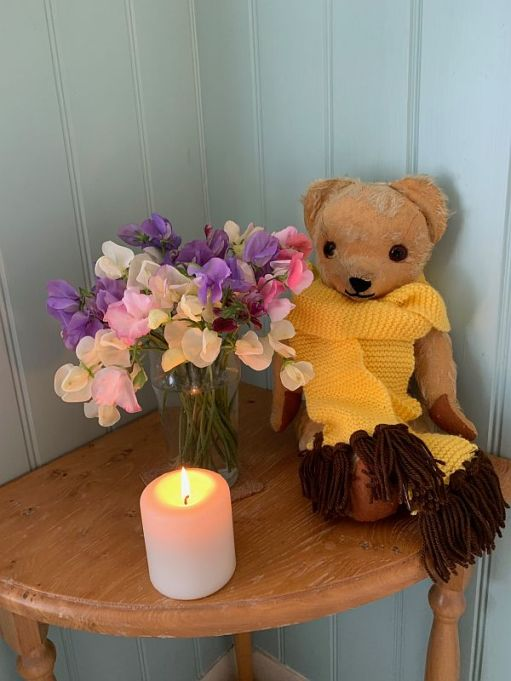 Eamonn in a yellow scarf with brown tassles next to a vase of colourful Sweet Peas. In front, a candle lit for Diddley.