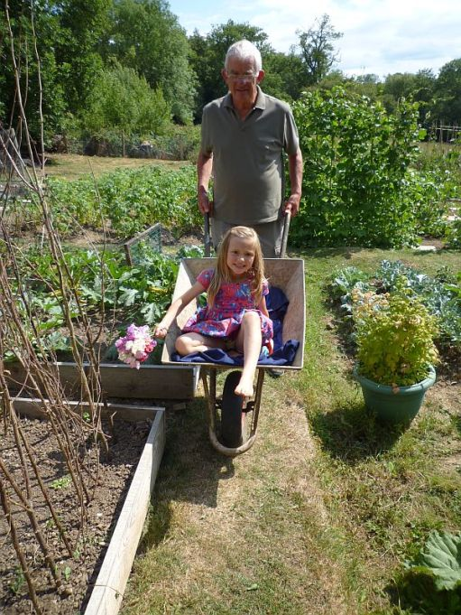 Layla being pushed by Bobby in his wheelbarrow.