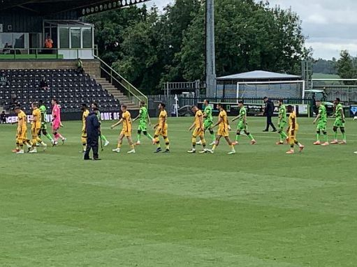 Sutton United in yellow and Forest Green in green emerge onto the pitch.
