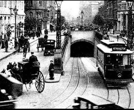 An electric single deck tram emerging from the Kingway Tram Tunnel amidst the horse-drawn carriages of the day.
