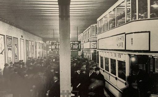 A white double-deck tram at a crowded Holborn tram stop in the Kingsway Tunnel for the special occassion of the opening of the new southern tunnel entrance.