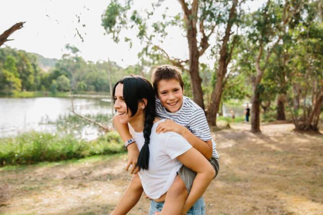 Tween boy has a piggyback ride with his mama