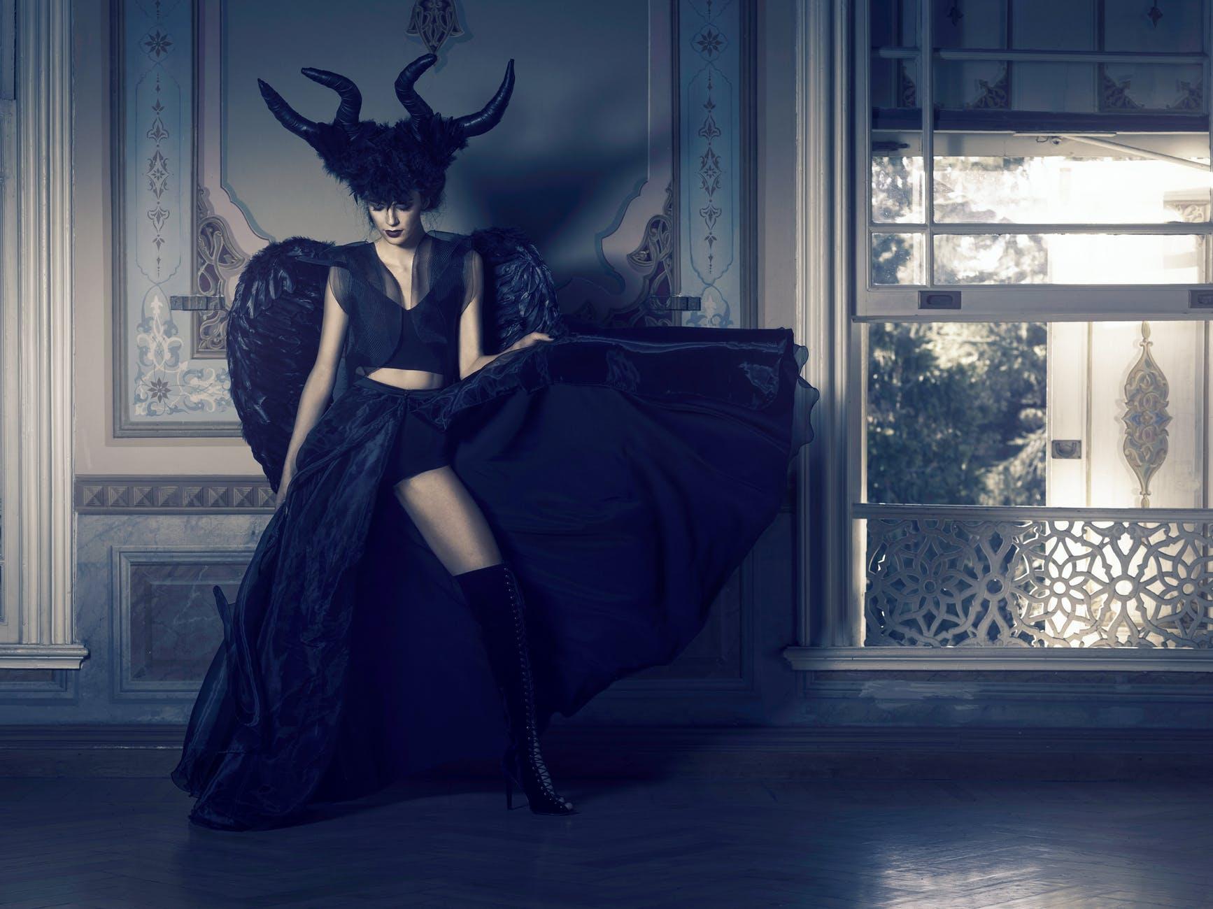 kobieta w czarnej sukni stojącej w pobliżu okna