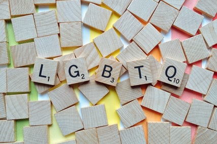 scrabble pieces on a rainbow background spelling L G B T Q