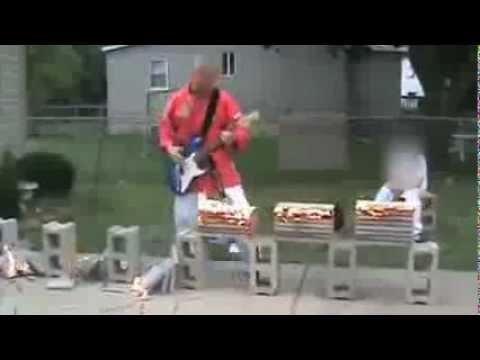 Typ zerschlägt E-Gitarre spielend brennende Ziegel