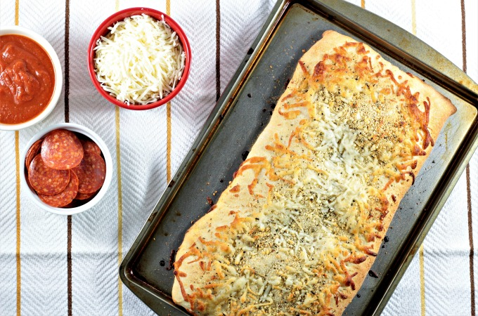 Pepperoni Stuffed Pizza Bread features premade crust, sauce, pepperoni, mozzarella & Parmesan cheese, Italian seasoning, and garlic powder. Easy and quick.