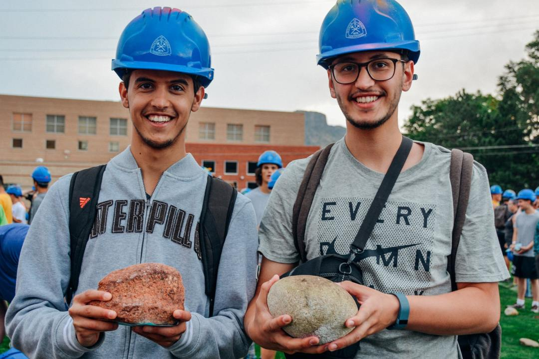 Two smiling students posing with miner's hats and rocks