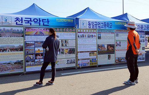 '马拉松活动场设置的天国乐团展位上,参赛选手们和市民们了解法轮功真相。'