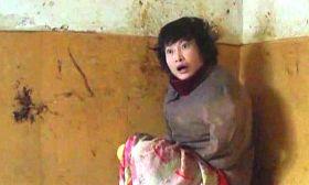 柳志梅常常不穿裤子,只裹一条单薄的床单坐在炕上。身后墙上的黑色黄色是她涂抹大便留下的印迹。(摄于二零一一年冬)