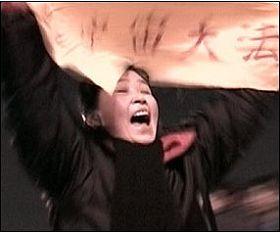 CNN: 一名女法轮功学员展开横幅高呼 为法轮功和平请愿