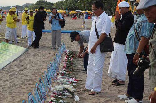 图6-11:游客们在被中共迫害致死的法轮功学员遗照前献花。