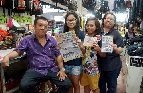 一家卖布料等用品的店铺老板刘先生(左一)与职员开心和照。
