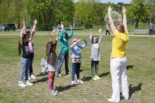 '图5~6:法轮功的功法吸引很多儿童公园里的孩子,纷纷一起学炼。'
