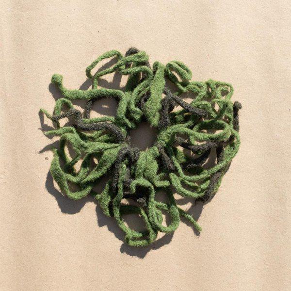 Rastarenksu-hiuslenkki, vihreitä villasuikaleita kiinnitettynä elastiseen hiuslenkkiin