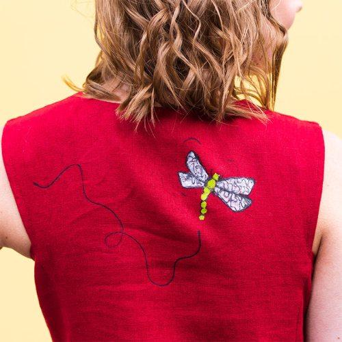 Punaisen pellavamekon selkäpuolella on sudenkorentomaalaus