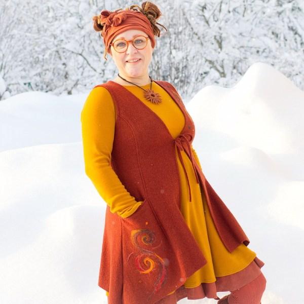 Ruosteenoranssi villainen liivi, jossa käsin huovutetut kuviot, puettuna lämpimän oranssin villaliivin alle. Minna Suuronen.